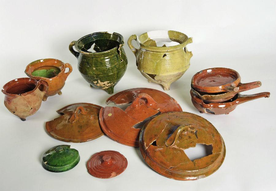 Koekenpannen, kookpotten en deksels van aardewerk uit de afvalput. (Archeologie West-Friesland)