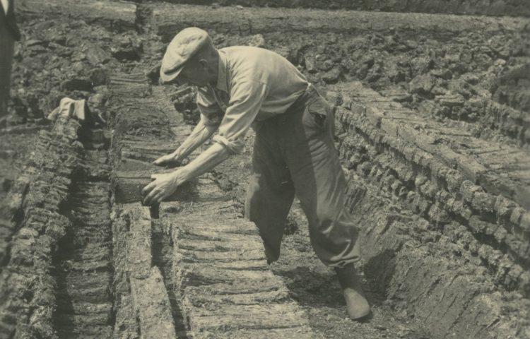 Een onbekende man bezig met het verstapelen van drogende fabrieksturf (laatste stadium) ten behoeve van ruilverkaveling Zegveld, provincie Utrecht. Deze foto is genomen in de gemeente Schoonebeek (Drents Archief)