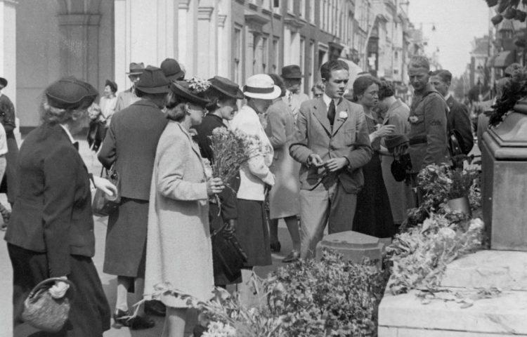 Anjerdag op 29 juni 1940, bij paleis Noordeinde, Den Haag. Als daad van verzet leggen burgers bloemen bij het standbeeld van Willem de Zwijger (Publiek Domein - Haags Gemeentearchief - wiki )
