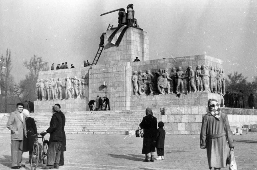 Demonstranten bevestigen een Hongaarse vlag op de plek van een ontmanteld Stalin-beeld, 1956 (CC BY-SA 3.0 - Fortepan - wiki)
