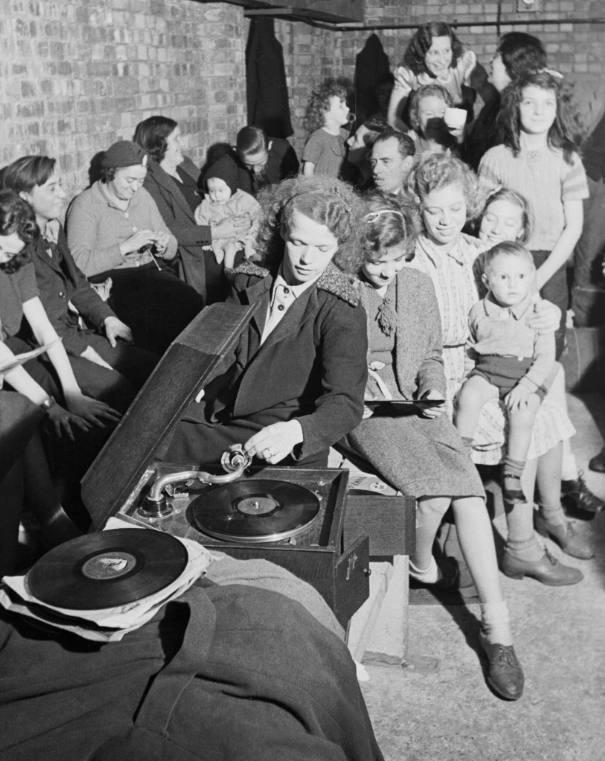 Een vrouw speelt een grammofoonplaat af in een schuilkelder tijdens een bombardement op Londen, 1940 (Publiek Domein - wiki)