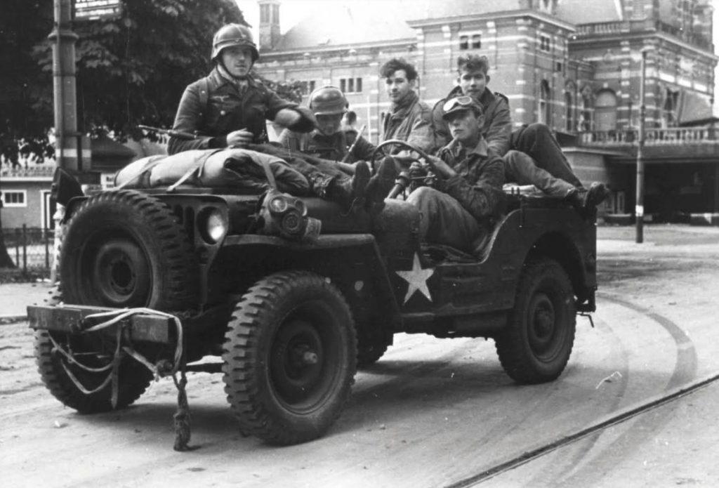 Duitse soldaten in een buitgemaakte Amerikaanse jeep in Arnhem. Jonge SS officieren hebben deze buitgemaakt, achterin zitten twee krijgsgevangen Britse parachutisten. (Bron: Oorlogsbronnen, collectie NIOD)