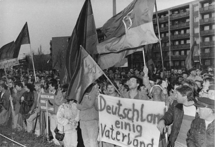 """Demonstranten met een spandoek met daarop de leus """"Deutschland einig Vaterland"""", december 1989 (Bundesarchiv / CC-BY-SA 3.0 / wiki)"""
