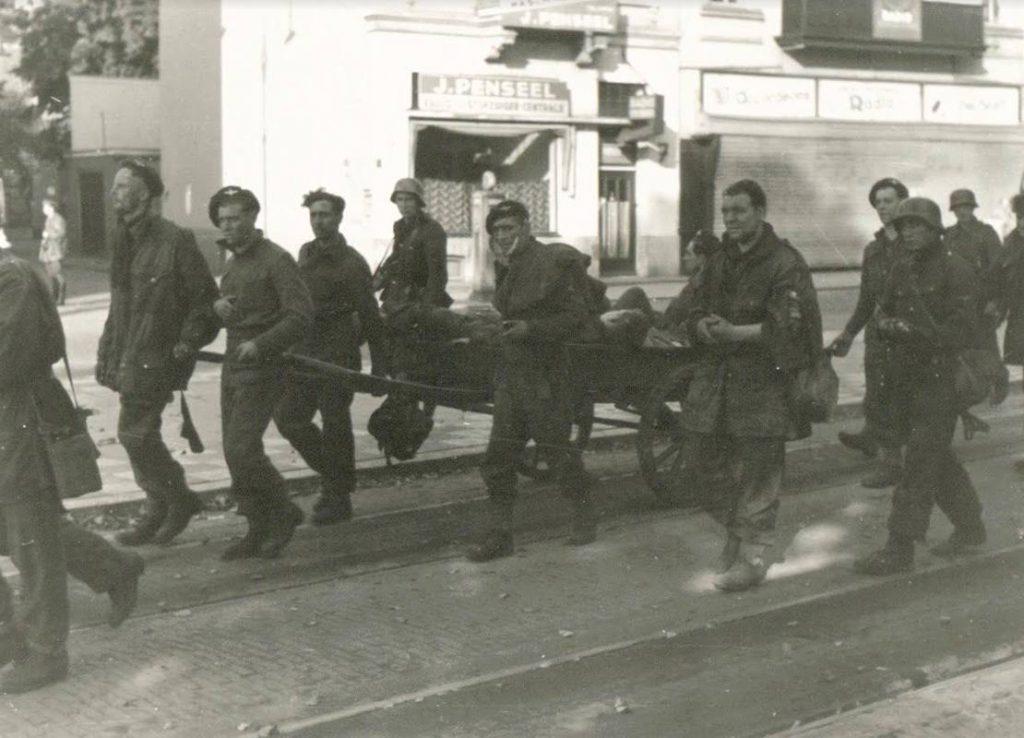 Britse krijgsgevangenen, waarvan een groot deel gewond, worden onder Duitse bewaking afgevoerd op de Jansbinnensingel in Arnhem. De foto is gemaakt tijdens Operatie Market Garden, op 19 september 1944. (Bron: Oorlogsbronnen, collectie NIMH)