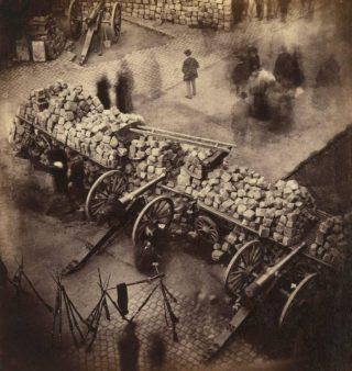 Door de Commune opgeworpen barricade, in de buurt van het Hotel de Ville - Pierre-Ambroise Richebourg (Publiek Domein - wiki)