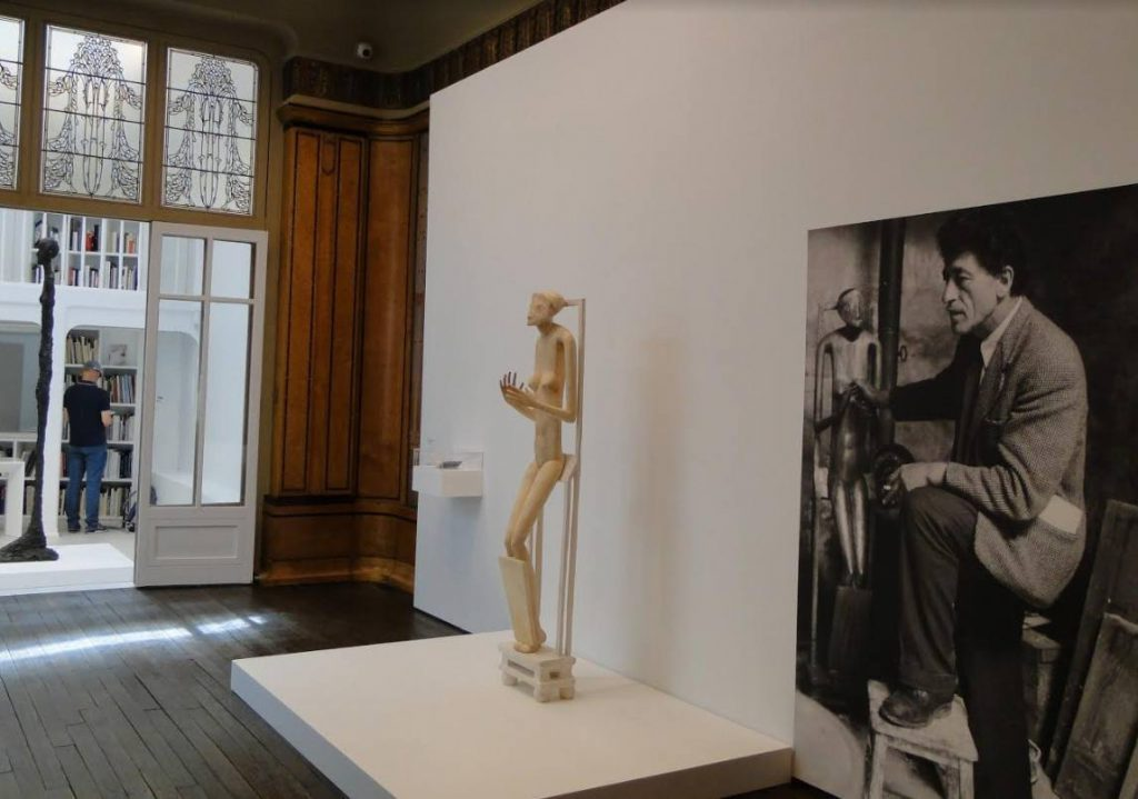 Werk van Giacometti met daarnaast een foto van de kunstenaar uit 1954