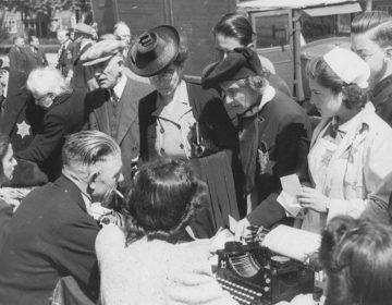 Medewerkers van de kampadministratie van kamp Westerbork schrijven op het Olympiaplein in Amsterdam (op de sportvelden) honderden joden in op 20 juni 1943, die daarna naar kamp Westerbork worden overgebracht. Foto: gemaakt door Herman Heukels (publiek domein). Beeldbank WO2, collectie NIOD.