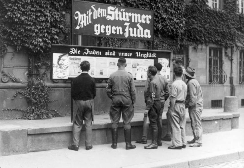 Voorbijgangers lezen in Worms artikelen uit Der Stürmer, 1933