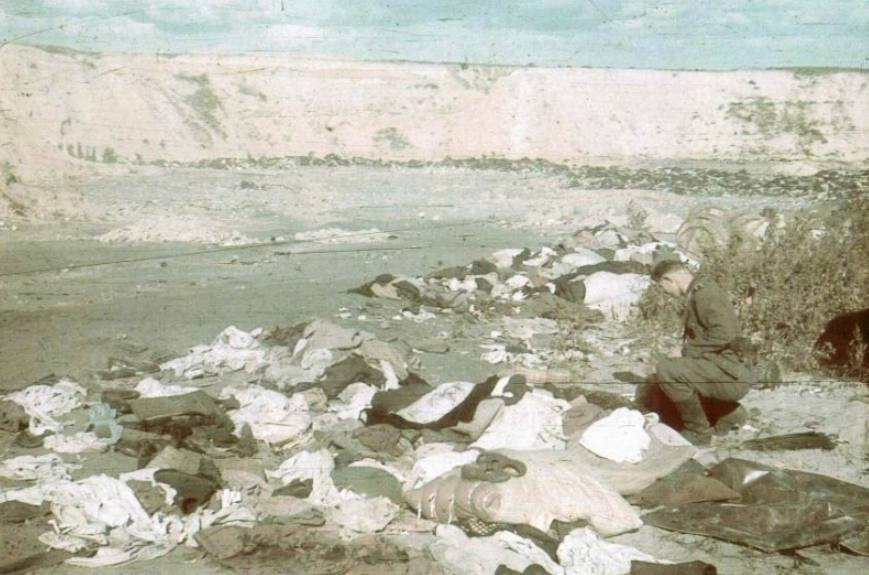 Een SS-soldaat doorzoekt bij Babi Jar de bezittingen die de Joden achter moesten laten voordat ze het ravijn ingedreven werden.