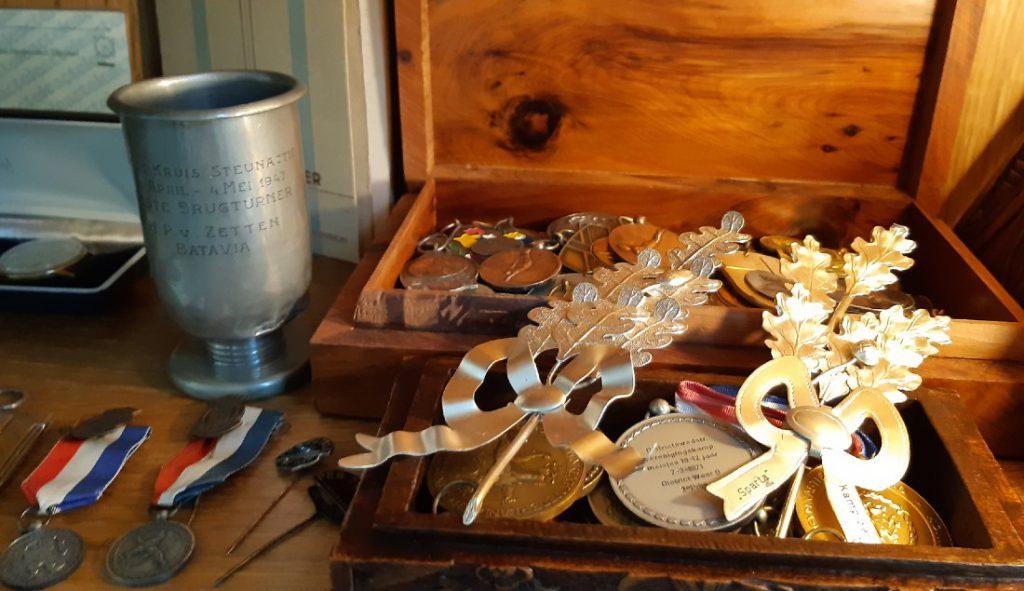 In een vitrinekast in de woning van Hans liggen medailles die familieleden in de loop der tijd met turnen wonnen. Links de beker van zijn vader Huib uit Batavia
