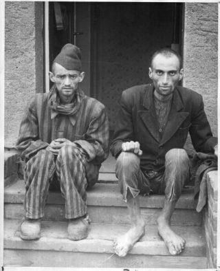 Twee overlevende concentratiekampgevangenen op de trappen van de Boelckekazerne.