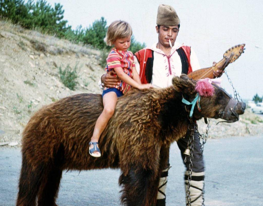 Kind op de rug van een 'dansende beer ' in Bulgarije, ca. 1970