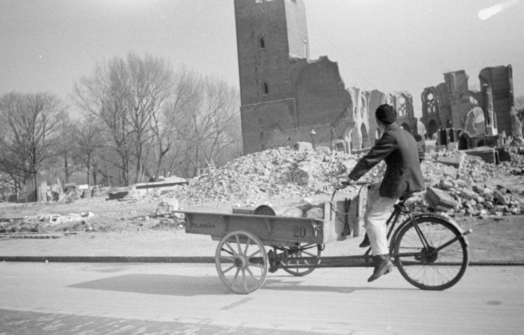 Een man rijdt met een bakfiets langs de ruïne van de vrijwel gesloopte R.K. kerk in Den Haag, op de hoek van de eveneens bijna gesloopte Stadhouderslaan wegens aanleg van de 'Atlantikwall'. - Menno Huizinga