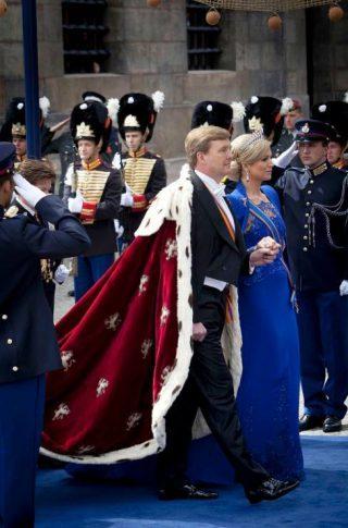 Koning Willem-Alexander en Koningin Maxima tijdens de inauguratie 2013 (CC0 - wiki - Gerben van Es/Ministerie van defensie) - Koning Willem-Alexander draagt een klassieke staatsiemantel uit rood fluweel, met hermelijnen voering en geborduurde leeuwtjes.