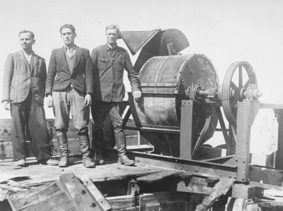 Leden van Sonderkommando 1005 naast een machine om botten te breken in concentratiekamp Janovska, 1943