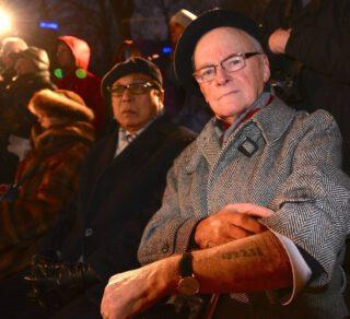 Een overlevende van de Holocaust laat tijdens een herdenking het op zijn arm getatoeëerde merkteken uit het concentratiekamp zien.