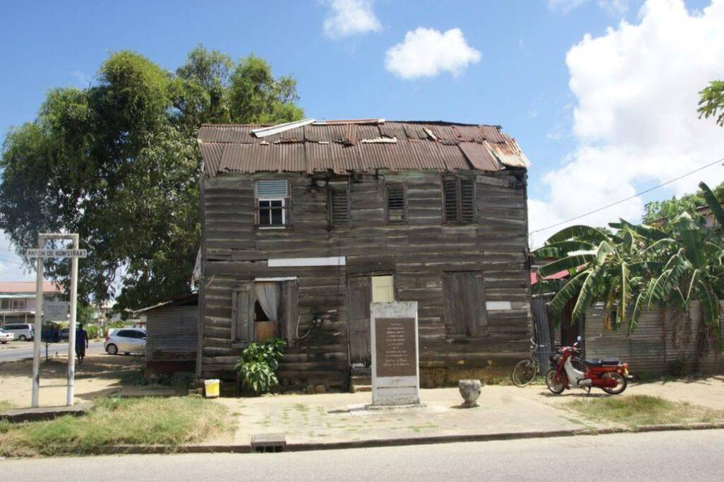 In 1985 werd bij het geboortehuis van Anton de Kom in Paramaribo een monument onthuld met de tekst Sranang mijn vaderland eenmaal hoop ik u weer te zien op de dag waarop alle ellende uit u weggewist zal zijn. Foto uit 2016