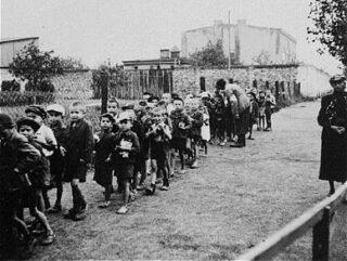 Kinderen in het getto van Łódź op weg naar de treinen die hen naar de vernietigingskampen brengen.