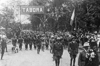 Belgische troepen met Belgische vlag, tijdens hun intrede in Tabora, 19 september 1916