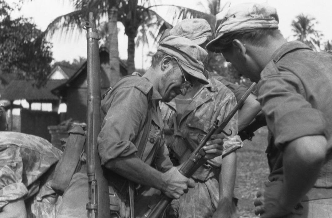 Een Nederlandse militair bevestigt een bajonet op de loop van een geweer, maart 1949