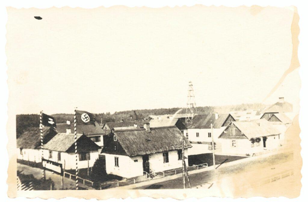 Blik vanaf de wachttoren bij de toegangspoort op het Vorlager, voorjaar 1943. Hier woonde het Duitse kamppersoneel. Op de achtergrond zijn daken te zien van Lager I, alsmede de arm van de graafmachine die vanaf najaar 1942 in Lager III lijken uit de bestaande massagraven haalde om ze te verbranden.