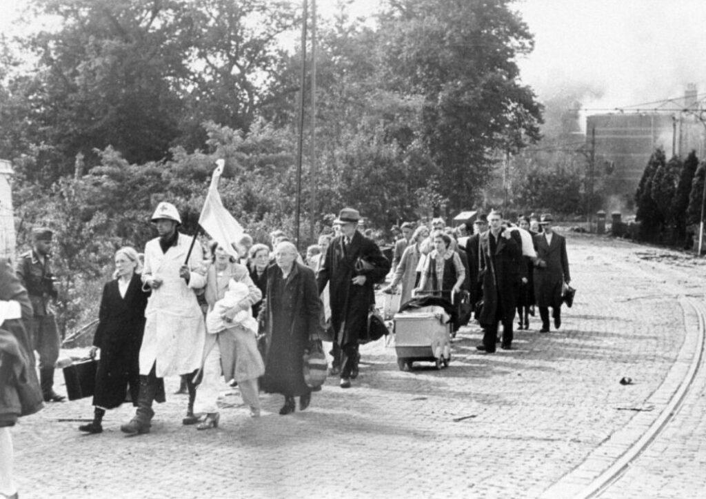 Evacués uit het Elisabethgasthuis onderweg, begeleid door een verpleegster met een witte vlag.