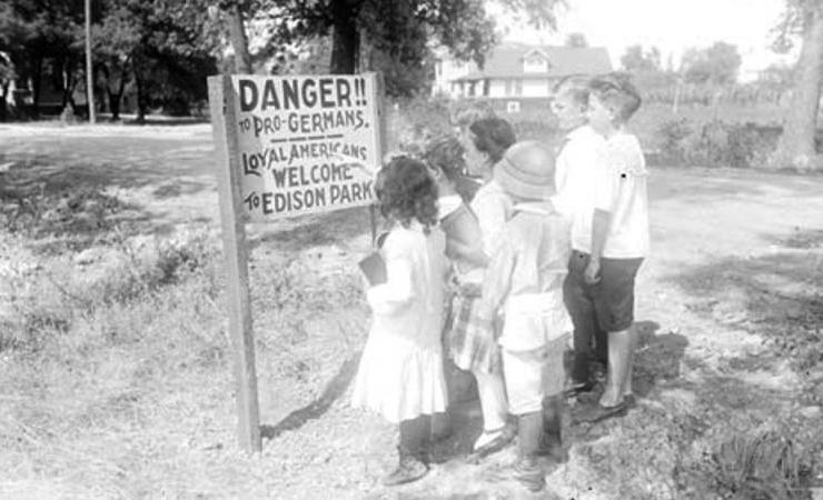Kinderen bestuderen een anti-Duits bord in een stadspark in Chicago. Het moet Duitslandsympathisanten afschrikken (1917). (Publiek domein/wiki)