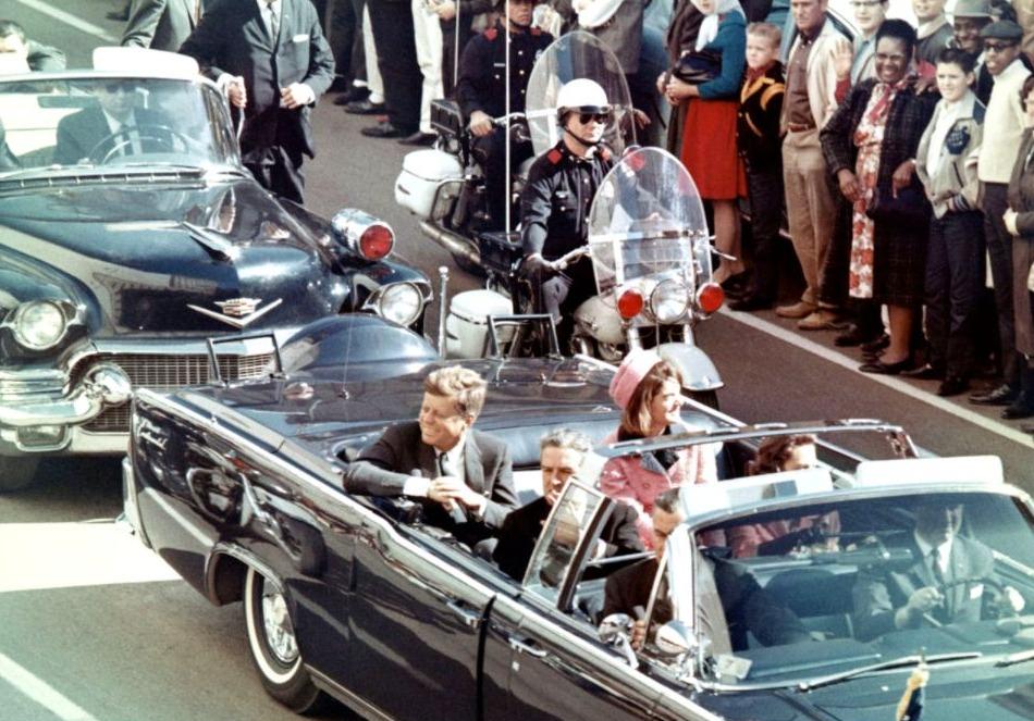 John F. Kennedy (links) en zijn vrouw in de limousine, kort voor de aanslag