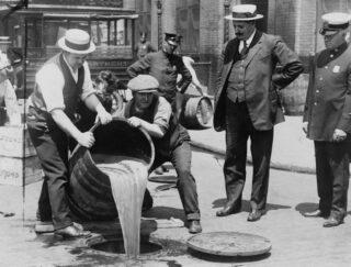 De politie laat tijdens de Drooglegging een vat vol alcohol in het riool storten