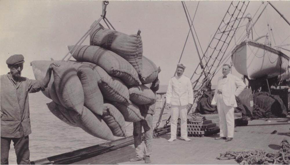 Zakken met koffiebonen worden in de haven van Les Cayes op Haïti aan boord gehesen. Fotoalbum van de familie Boom-Gonggrijp, plantagehouders in Suriname en Curaçao, 1912. Rijksmuseum Amsterdam