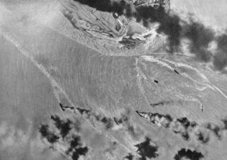Luchtfoto van brandende schepen in de haven van Darwin na de eerste Japanse aanvalsgolf