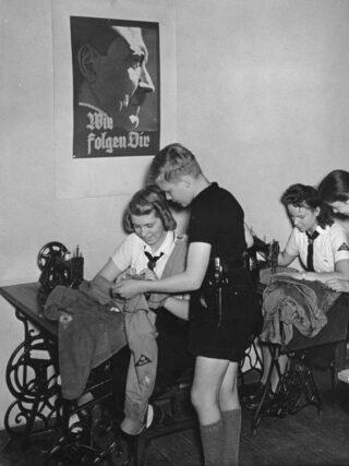BDM-meisjes naaien kleding. Aan de wand een portret van Adolf Hitler
