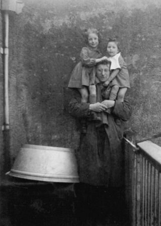 1952. Zus Marjolein en Catherine op de schouders van hun vader, op het balkon. Het gezin woonde toen op de Zuidwal in Den Haag.