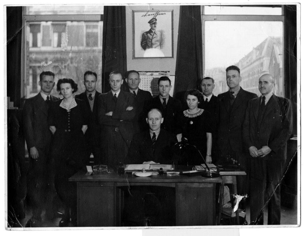 De mini-Gestapo van de Haarlemse politie begin 1944. Jan van Bragt was toen nog niet in vaste dienst. Derde van rechts Fake Krist. Na de oorlog werd op het portret van Adolf Hitler 'chauffeur'geschreven. Foto Nationaal Archief