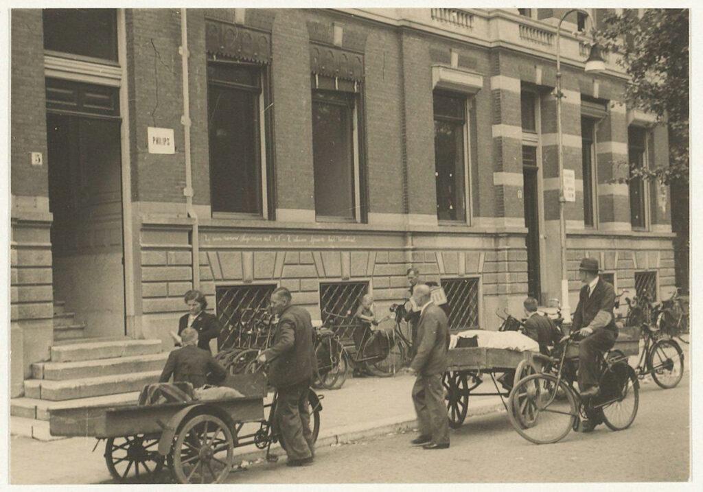 Haarlemmers komen in 1943 bij het Haarlemse politiebureau aan het Nassauplein, waar de mini-Gestapo zetelt, hun radio's inleveren. Foto Noord-Hollands Archief