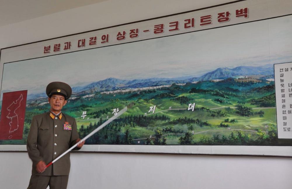Een Noord-Koreaanse official wijst op een landkaart de scheiding tussen Noord- en Zuid-Korea aan