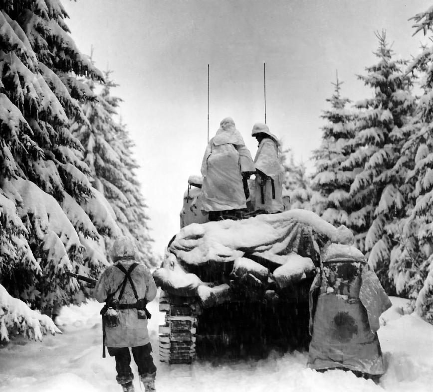 Ardennenoffensief - Amerikaanse soldaten nemen een M4 Sherman-tank om zich te verplaatsen.