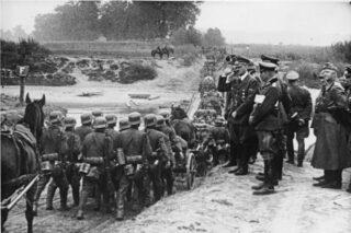 Hitler kijkt toe hoe Duitse soldaten Polen in marcheren