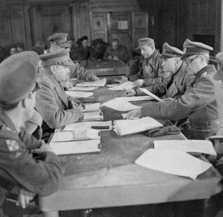 Bespreking in Hotel de Wereld in Wageningen, 5 mei 1945. Midden links Charles Foulkes, geheel links vooraan Prins Bernhard; midden rechts Johannes Blaskowitz.