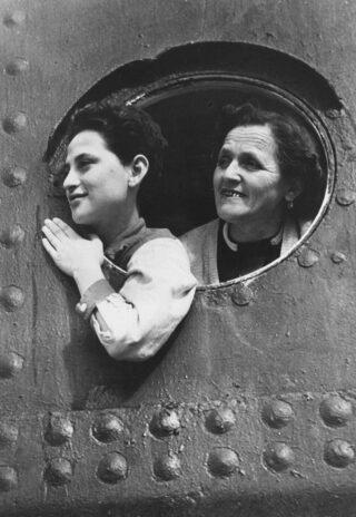 Twee passagiers te zien in een patrijspoort van de St. Louis