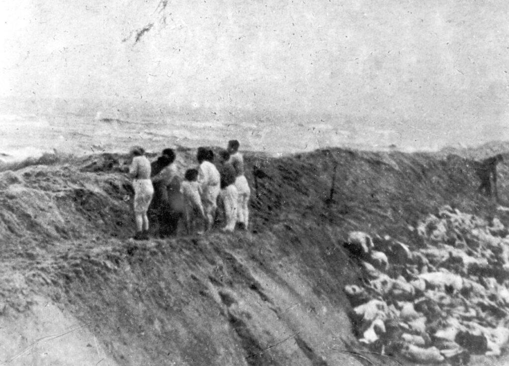 'Joodse vrouwen en kinderen uit Liepāja staan op de rand van een put vooraleer vermoord te worden, 15 december 1941 – foto gemaakt door Oberscharführer Carl-Emil Strott (Yad Vashem Photo Archive, Jerusalem, archival signature 1979/5).