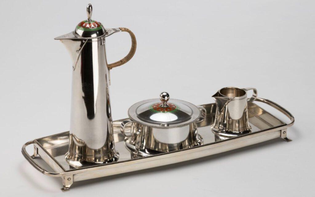 Jan Eisenloeffel (1876-1957) (ontwerp) / Fa C.J. Begeer, Utrecht (uitvoering), Mokkaservies op blad, 1906, zilver, email en rotan