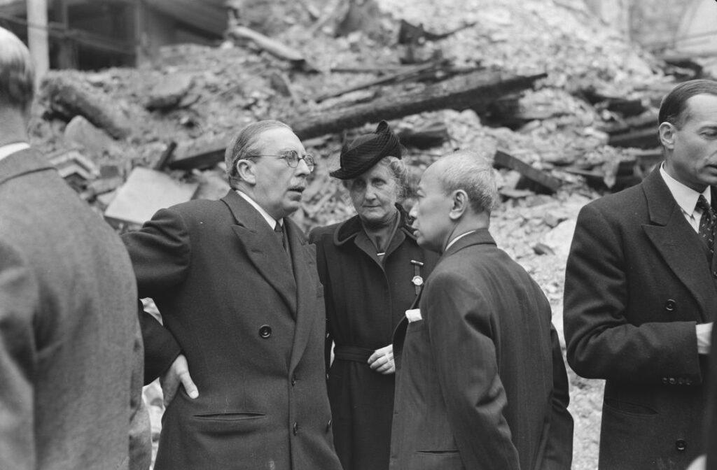 Soejono (rechts) spreekt met de Nederlandse ambassadeur in Londen, Michiels van Verduynen, en diens vrouw bij de ruïne van de Nederlandse kerk in Austin Friars. Het is 10 mei 1942, een maand voor Soejono's aantreden als minister.