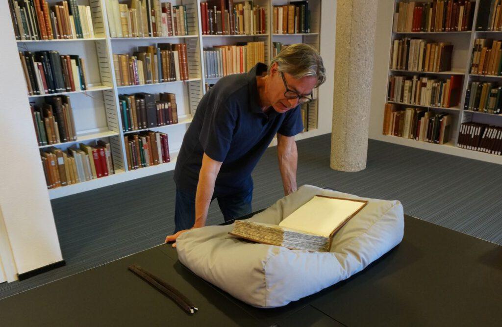 De auteur bij de oude Leidse codex, de Codex Sarravianus in de Universiteitsbibliotheek (Archief TB)