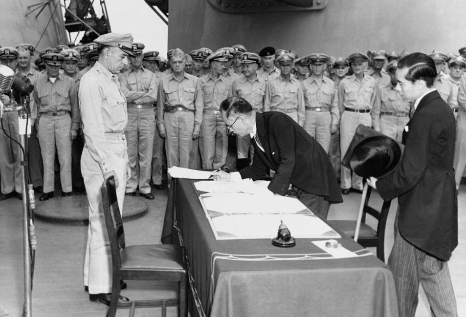 De Japanse buitenlandminister Mamoru Shigemitsu ondertekent het overgave-document aan boord van de USS Missouri, terwijl generaal Richard K. Sutherland toekijkt, 2 september 1945