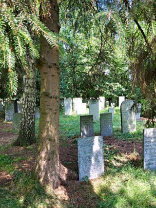 Meer dan 100 jaar oude grafmonumenten in de schaduw van bomen geven de plek een authentieke uitstraling.