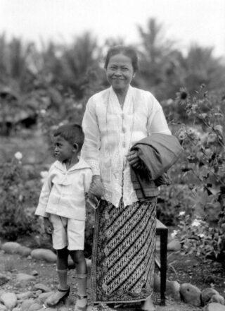 Portret van een vrouw in sarong en kabaja met kind aan de hand.  (CC BY-SA 3.0 – Tropenmuseum – wiki)